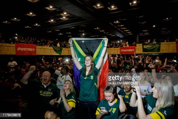 A woman holds a South African flag as South Africans celebrate after South Africa won the Rugby World Cup 2019 Final between South Africa and England...