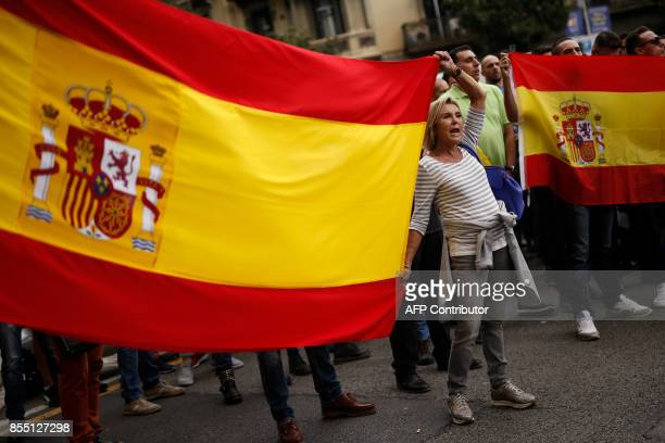 A woman holds a Spanish flag as she protest with members of the Spanish National Police and Civil Guard during a demonstration called by the 'Fair...