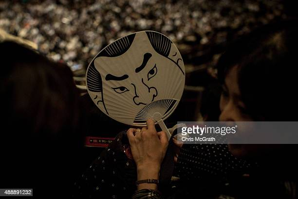 A woman holds a sumo styled fan during the Tokyo Grand Sumo tournament at the Ryogoku Kokugikan on September 16 2015 in Tokyo Japan Japanese Sumo is...