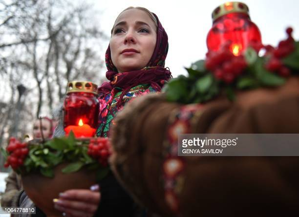 A woman holds a symbolic bowl of wheat and candles during a commemoration ceremony at a monument to victims of the Holodomor famine of 193233 in Kiev...