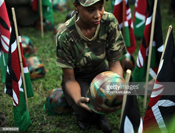 A woman holds a symbolic helmet among Kenyan flags at a vigil on January 21 2015 in Nairobi in honour of Kenya Defence Forces soldiers killed on an...