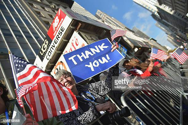 A woman holds a thank you sign while watching the annual Veterans Day Parade aka America's Parade on November 11 2014 in New York City The parade...
