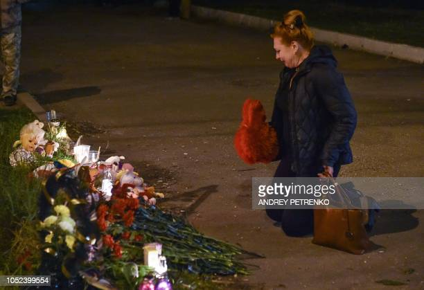 A woman holds a toy as she lays flowers near a college in Kerch Crimea on October 17 after a student opened fire at a technical college in the...