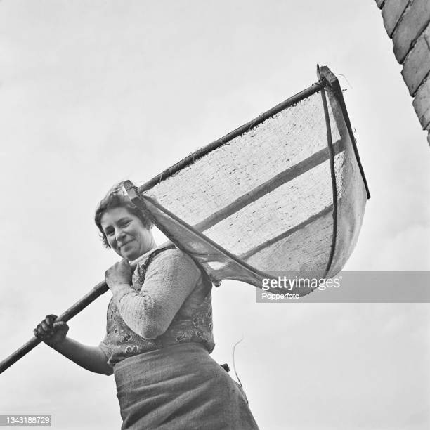 Woman holds a traditional wooden willow net for catching eels and elvers beside a waterway on the Somerset Levels in Somerset, England on 1st April...
