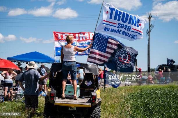 Woman holds a Trump 2020 flag and a Q Anon flag outside of Mankato Regional Airport as President Donald Trump makes a campaign stop on August 17,...