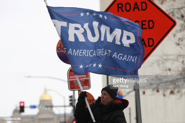 A woman holds a Trump flag on the street February 3 2020 in Des Moines Iowa Iowans will pick their choices for Democratic presidential candidate at...