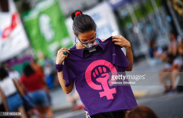 Woman holds a t-shirt with a feminist symbol as she takes part in a demonstration to mark the International Women's Day outside the Congress on March...