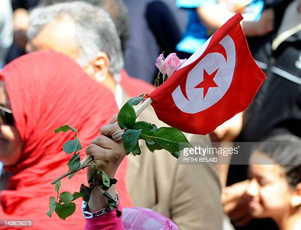 A woman holds a Tunisian flag and a flower as she joins tens of thousands of Tunisians marching for national unity during a May day rally in Tunis on...