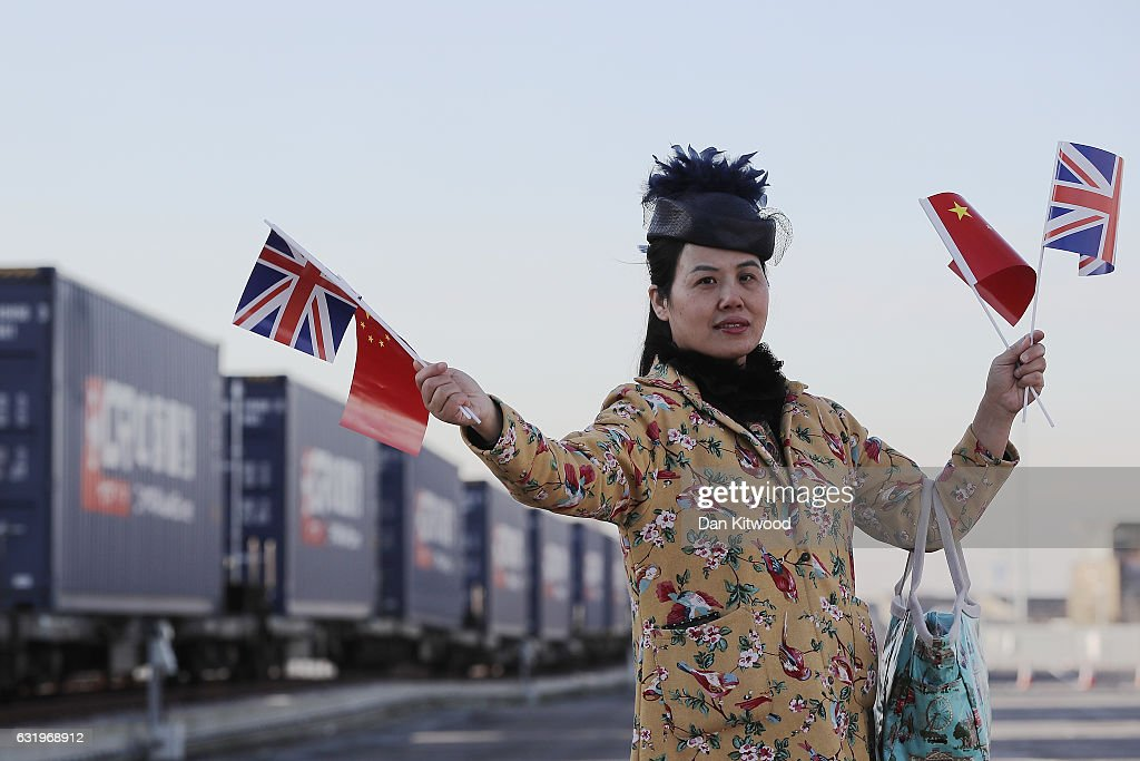 A woman holds a Union flag and a Chinese Flag as a train engine pulls carriages that started their Journey in Yiwu in China into Barking rail freight terminal on January 18, 2017 in Barking, England. After travelling for 16 days and covering around 7,456 miles passing through China, Kazakhstan, Russia, Belarus, Poland, Germany, Belgium and France, The East Wind freight train which is made up of 34 wagons is hoped will herald a 'new era of UK-China relations'. The Engine that started the journey was changed to accomodate different gauge tracks in the UK.