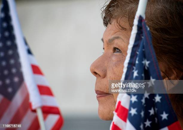 A woman holds a US flag as members of the November 2020 Coalition protest outside the Federal Building calling for the Trump administration to close...