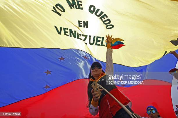 TOPSHOT A woman holds a Venezuelan flag as she wtakes part in the Venezuela Aid Live concert organized by British billionaire Richard Branson to...