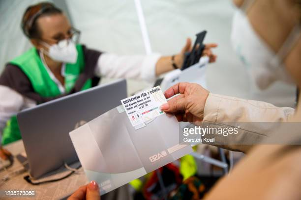 Woman holds a voucher for a doner kebab after receiving a dose of the Moderna vaccine in a temporary vaccination center, where , on the third day of...