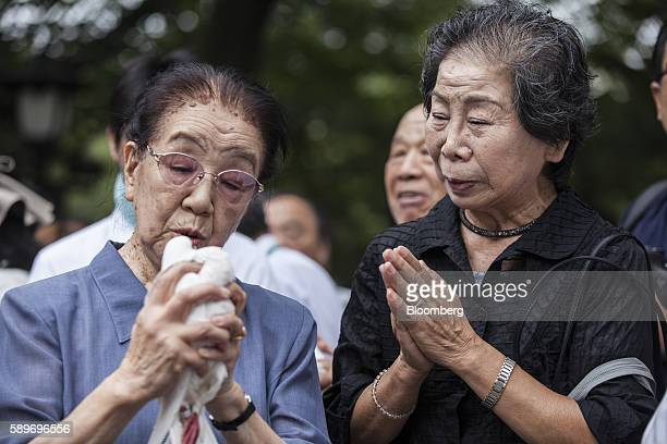 A woman holds a white dove before releasing it as a tribute to the war dead at the Yasukuni Shrine on the anniversary of Japan's World War II...