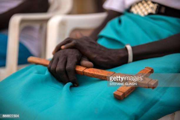 A woman holds a wooden cross during a prayer session at Tomping Presbyterian Church after taking part in a silent march with women from more than...