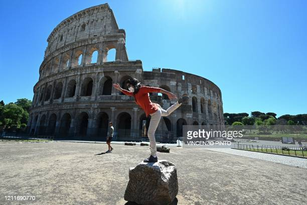 Woman holds a yoga posture as she exercises by the Colosseum monument in Rome on May 4 as Italy starts to ease its lockdown, during the country's...