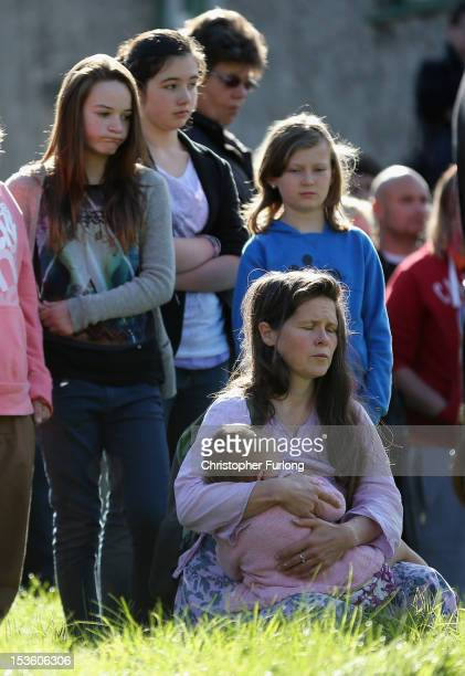 A woman holds a young child as members of the community of Machynlleth stand in the church yard of St Peter's Church for a service with prayers for...