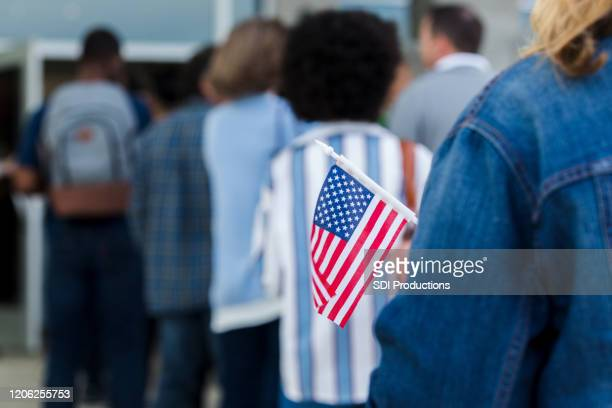 woman holds american flag on election day - presidential election stock pictures, royalty-free photos & images