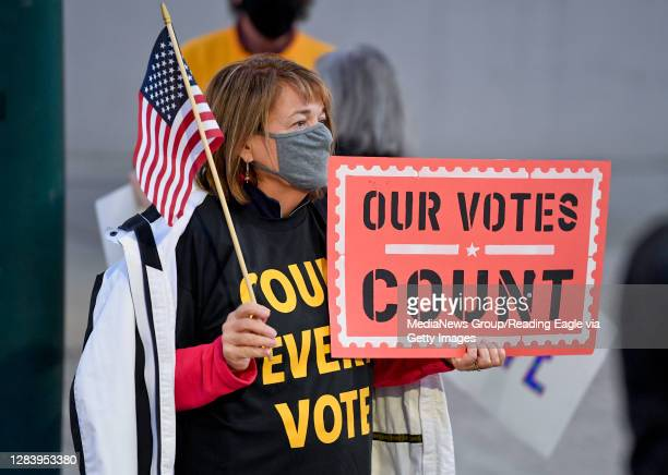 "Woman holds an American Flag, and a sign that reads ""Our Votes Count"". At 5th and Penn Streets in Reading, PA Wednesday evening November 4, 2020..."