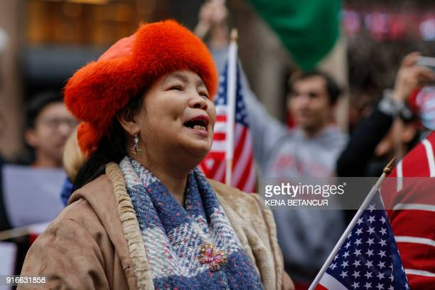 A woman holds an american flag as she attends a protest in support of immigration in herald Square on February 10 2018 in New York / AFP PHOTO / KENA...
