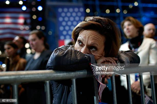 A woman holds an American flag as she watches the voting results at Democratic presidential nominee former Secretary of State Hillary Clinton's...