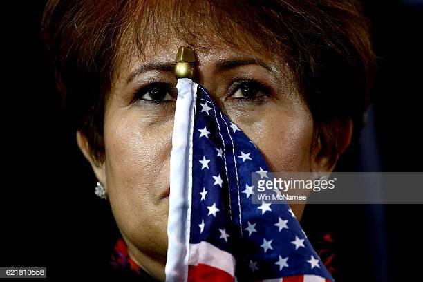 Woman holds an American flag to her face as she watches the voting results at Democratic presidential nominee former Secretary of State Hillary...