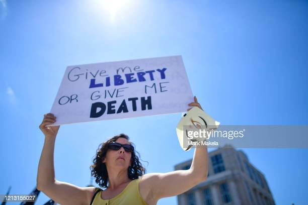 A woman holds an Anonymous mask and a placard stating Give me LIBERTY OR GIVE ME DEATH while joining demonstrators at a rally outside the...