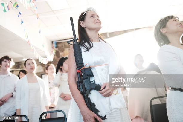 A woman holds an AR15 rifle during a ceremony at the World Peace and Unification Sanctuary on February 28 2018 in Newfoundland Pennsylvania The...
