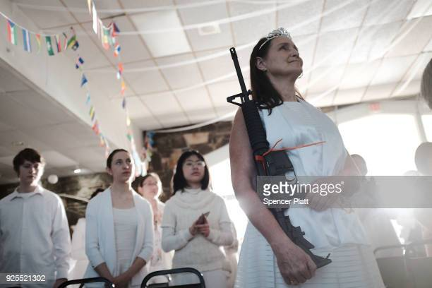 A woman holds an AR15 rifle during a ceremony at the World Peace and Unification Sanctuary in Newfoundland Pennsylvania on February 28 2018 in...