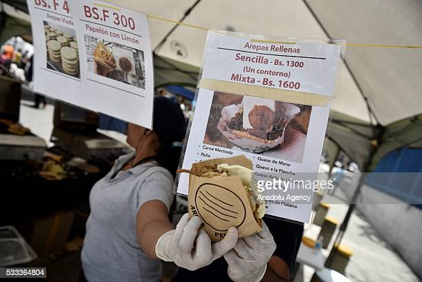 A woman holds an arepa a local tortilla stuffed with protein at a market in Caracas Venezuela on May 21 2016 The arepa is considerer the typical...