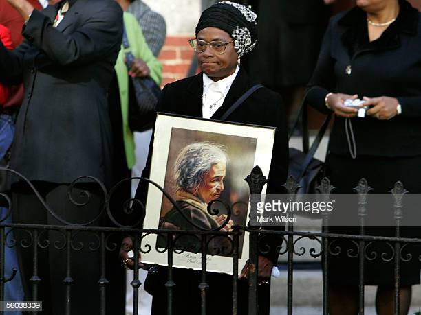 A woman holds an artist's rendering of Rosa Parks in front of the Metropolitan AME Church where a memorial service for the civil rights icon was...