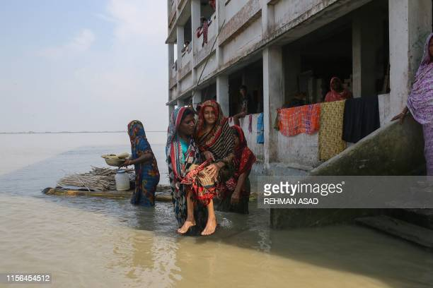 Woman holds an elderly following heavy monsoon rains at a flood affected area of Gaibandha District, in Northern Bangladesh, on July 19, 2019. -...
