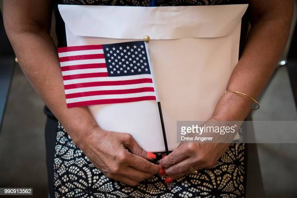 A woman holds an flag and her citizenship packet during a naturalization ceremony at the New York Public Library July 3 2018 in New York City 200...