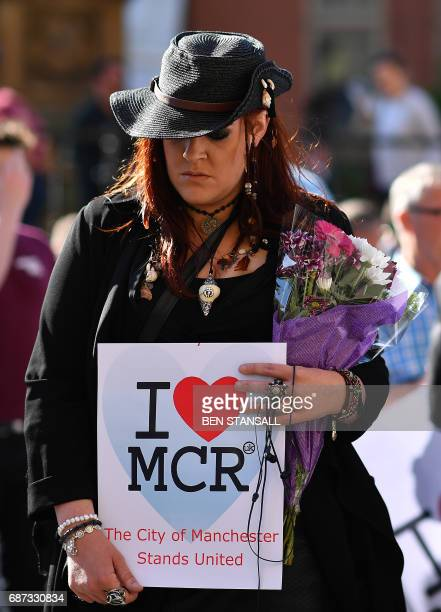 A woman holds an 'I love MCR' banner as she arrives to attend a vigil in Albert Square in Manchester northwest England on May 23 in solidarity with...