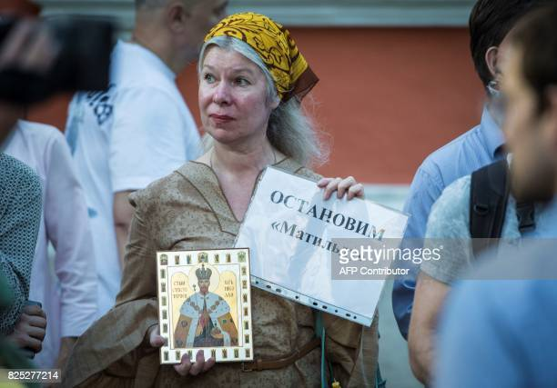 A woman holds an icon of the canonised last Russian Tsar Nikolay II and a sign reading 'stop Matilda' during a protest against the movie 'Matilda' at...
