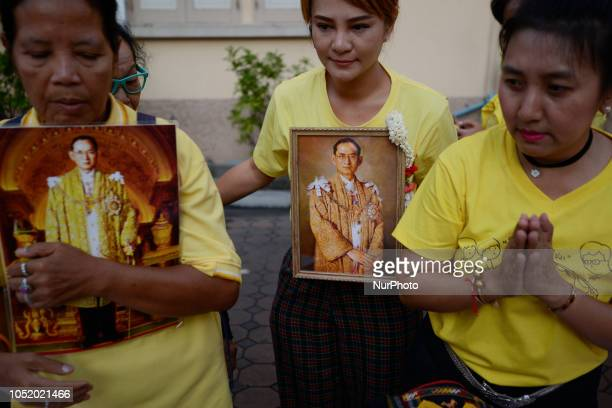 A woman holds an image of late Thai King Bhumibol Adulyadej during a making 2 year anniversary of the Thai King Bhumibol Adulyadej's death at Siriraj...