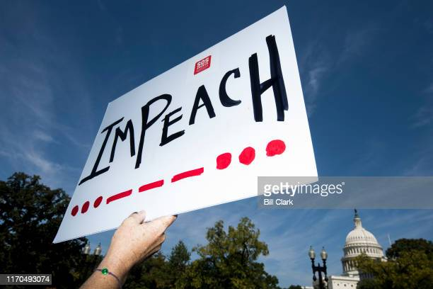 A woman holds an impeach sign as Rep Al Green DTexas and Rep Rashida Tlaib DMich speak to a group of protesters and the media about the need to...
