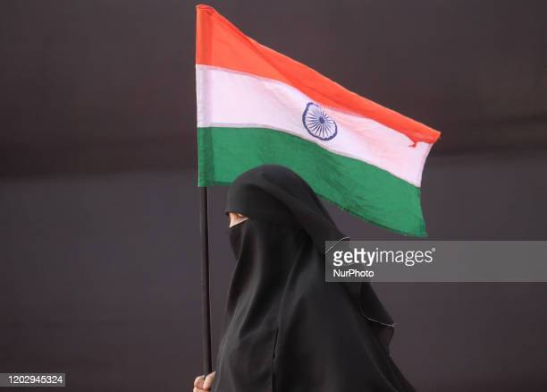 A woman holds an Indian national flag during a protest against the Citizenship Amendment Act and National Register of Citizens and National...