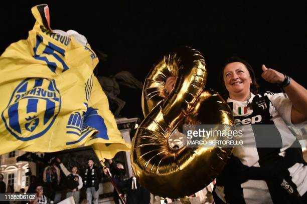 A woman holds an inflatable number 8 as Juventus fans celebrate in downtown Turin after Juventus secured its 8th consecutive Italian 2018/19 Scudetto...