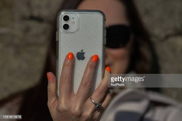 Woman holds an iPhone in Dún Laoghaire, Dublin, during Level 5 Covid-19 lockdown. On Sunday, 21 March in Dublin, Ireland.