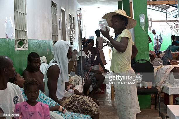 A woman holds an IV drip for her son suffering from cholera at the Charles Colimon hospital in Petite Riviere on the Artibonite river believed to be...