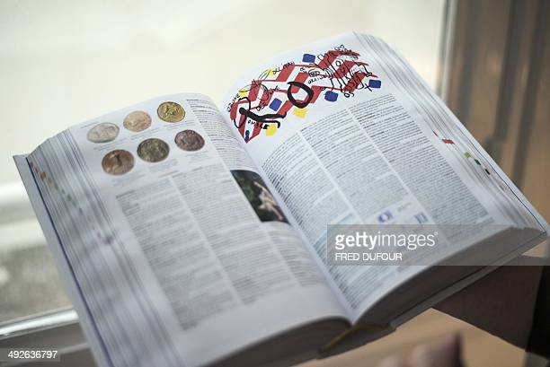 A woman holds an open copy of the newly printed 2015 edition of the French Petit Larousse dictionary on May 21 in Paris The Petit Larousse is marking...