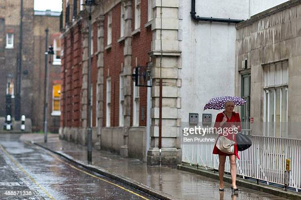 A woman holds an umbrella as she shelters from the rain on September 16 2015 in London England Tropical Storm Henri has been downgraded to an...