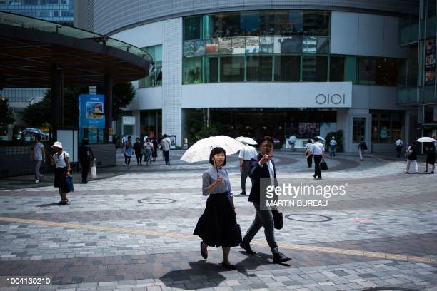 A woman holds an umbrella as she walks along a street in Tokyo on July 23 as Japan suffers from a heatwave Japan's severe heatwave killed at least 15...