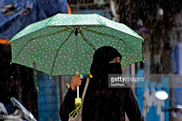A woman holds an umbrella as the the cyclonic storm Fani hits the coastal places of Orissa and West Bengal on 03 May 2019 Due to the cyclonic storm...