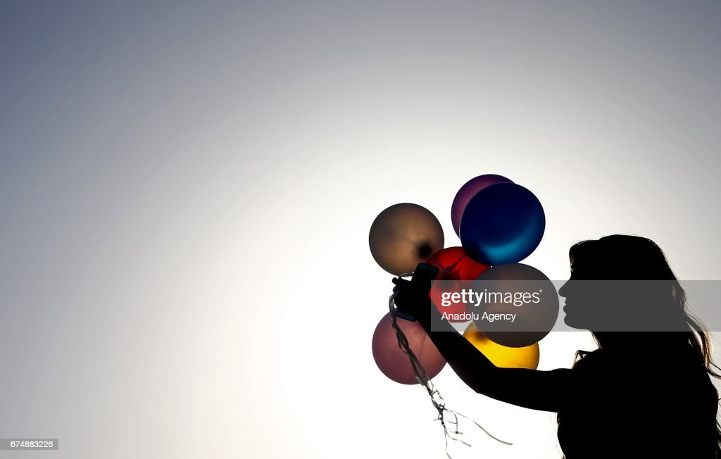A woman holds balloons during the sunset at a beach in Antalya, Turkey on April 29, 2017.