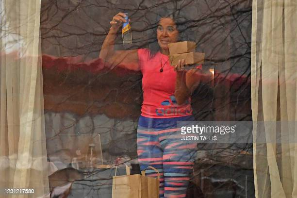 Woman holds boxes and a bottled drink as she looks out of a window from inside the Radisson Blu hotel at Heathrow Airport in west London on February...