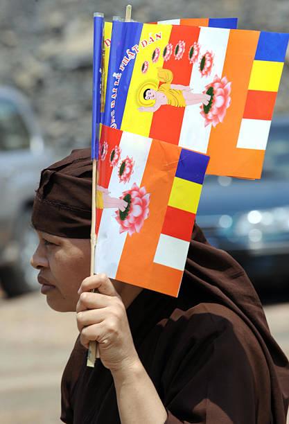 A Woman Holds Buddhist Flags As She Arri