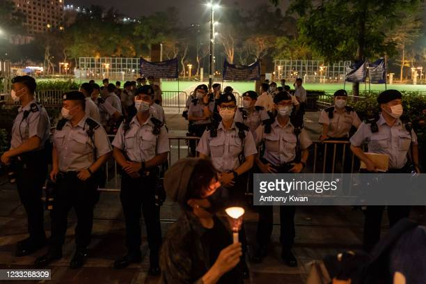 Woman holds candle as she walks in front of the Victoria Park after police closed the venue where Hong Kong people traditionally gather annually to...