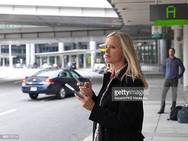 Woman holds cell phone & address book,airport term