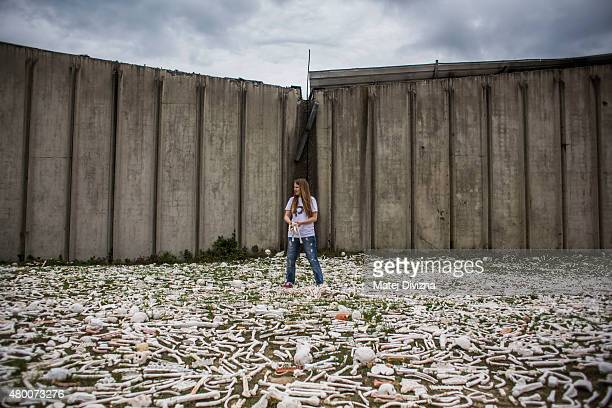 A woman holds ceramic bones as part of 'The One Million Bones' project in front of the hall at the Potocari cemetery and memorial near Srebrenica on...
